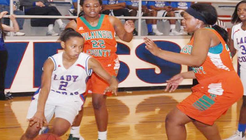 DAILY LEADER / TRACY FISCHER / Wesson's Aurianna Vaughn (2) dribbles past Wilkinson County's Freddricka Scott (24) and Gadrieka Cotton (22) in Region 7-3A action Saturday.
