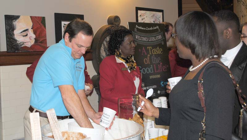 Mark Crosby of the Mississippi Ice Cream Factory in Brookhaven scoops some ice cream for Mildred Michael from Mississippi Valley State University at the Brookhaven Day at the Capitol social event Tuesday.