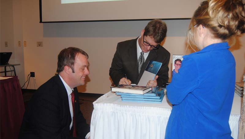 THE DAILY LEADER / KIM HENDERSON / Wesson Mayor Alton Shaw (left) waits as Marshall Ramsey signs a copy of his book following Tuesday night's Wesson Chamber banquet at the Thames Conference Center at Copiah-Lincoln Community College.
