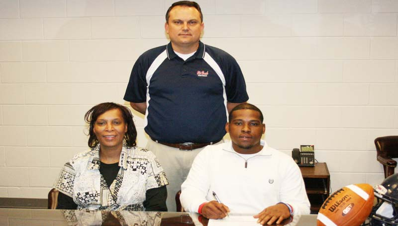 DAILY LEADER / MARTY ALBRIGHT /  Hill SIGNS WITH JONES COUNTY - Brookhaven defensive linebacker Tyris Hill has signed with the Jones County Community College Bobcats. Pictured with Hill are his mother Phyllis Hill (left) and (standing) Brookhaven head coach Tommy Clopton.