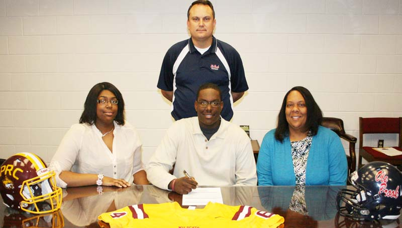 DAILY LEADER / MARTY ALBRIGHT / NELSON SIGNS WITH PEARL RIVER - Brookhaven offensive lineman Keefa Nelson has signed with the Pearl River Community College Wildcats. Pictured with Nelson are his sister, Erica Nelson, (left) his mother, Ursula Nelson, and (standing) Brookhaven head coach Tommy Clopton.