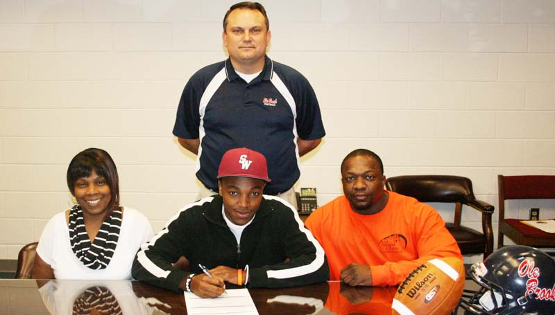 DAILY LEADER / MARTY ALBRIGHT /  SMITH SIGNS WITH SOUTHWEST - Brookhaven receiver and special team specialist Shuntez Smith has signed with the Southwest Community College Bears. Pictured with Smith are his mother Teresa Smith, (left) his dad, Gregory James, and (standing) Brookhaven head coach Tommy Clopton.