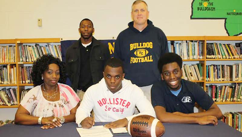 DAILY LEADER / STEPHANIE MCCORMICK / ROBINSON SIGNS WITH GULF COAST - Franklin County running back Chris Robinson has signed with the Mississippi Gulf Coast Community College Bulldogs. Pictured with Robinson are his mother, Rachel Harris; brother, Ken Robinson; and (standing) Franklin County coaches Jonathan Brooks and Adam Barron.