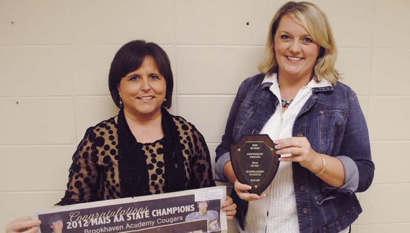 DAILY LEADER / JUSTIN VICORY / Brookhaven Academy Headmaster Julie Wright (left) holds The Daily Leader's first-place winning ad that saluted the BA football team on winning the 2012 state championship, while Kristi Carver, Daily Leader advertising department, holds the first place award plaque.