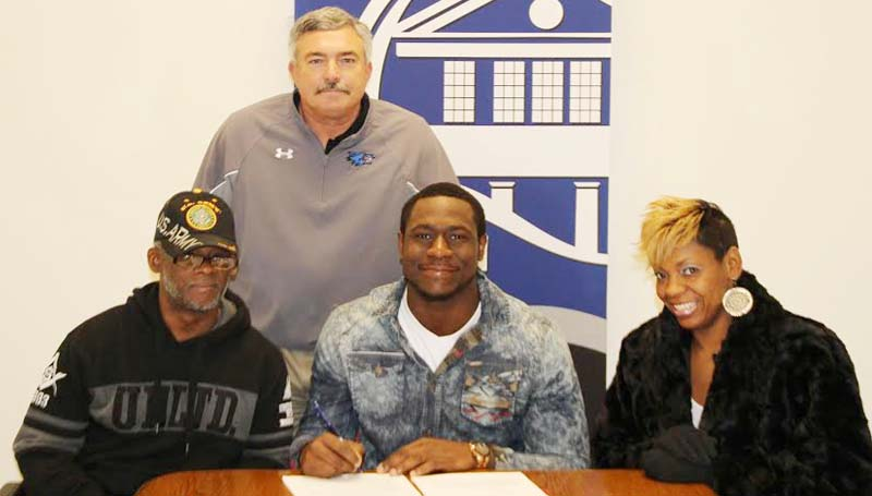 CO-LIN MEDIA / NATALIE DAVIS / PHILLIPS SIGNS WITH ILLINOIS - Copiah-Lincoln Community College (Miss.) defensive lineman Caroll Phillips of Miami, Fla., has signed with the University of Illinois. Pictured with Phillips is his uncle, Kevin Adderly of Nashville, Tenn.; his mother Ta-Tanisha Brown of Miami and Co-Lin head coach Glenn Davis (standing).