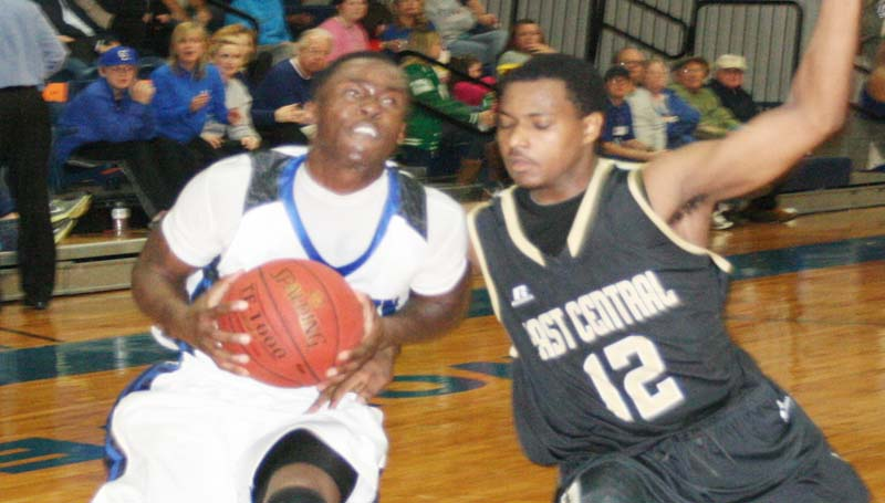 DAILY LEADER / MARTY ALBRIGHT / Co-Lin's Michael Vardaman (left) drives past East Central's Ramone Tate (12) Thursday night in men's action.