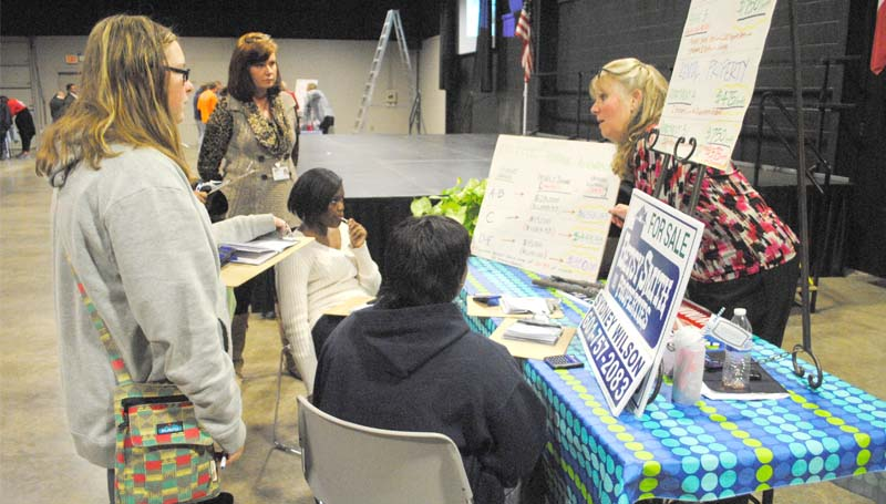 """THE DAILY LEADER / RHONDA DUNAWAY / Sydney Wilson with Betsy Smith Properties of Brookhaven (standing right) explains to students Anna Martin (standing left), Dominique McWillie (seated facing) and Khaiesha Lindsey, all of Brookhaven High School, the steps required in purchasing a home and the differences in buying versus renting. The presentation was a part of """"Reality World"""" at the Lincoln Civic Center Thursday."""