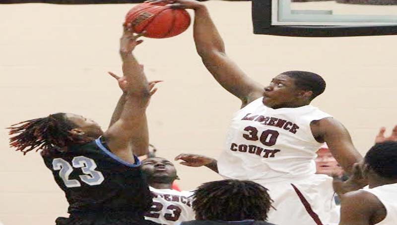 DAILY LEADER / JONATHON ALFORD / Lawrence County's La'Brian Bass (30) collects a monstrous block for the Cougars against North Pike's D'Hendrick Wells (23) and goes in for a layup Friday night.