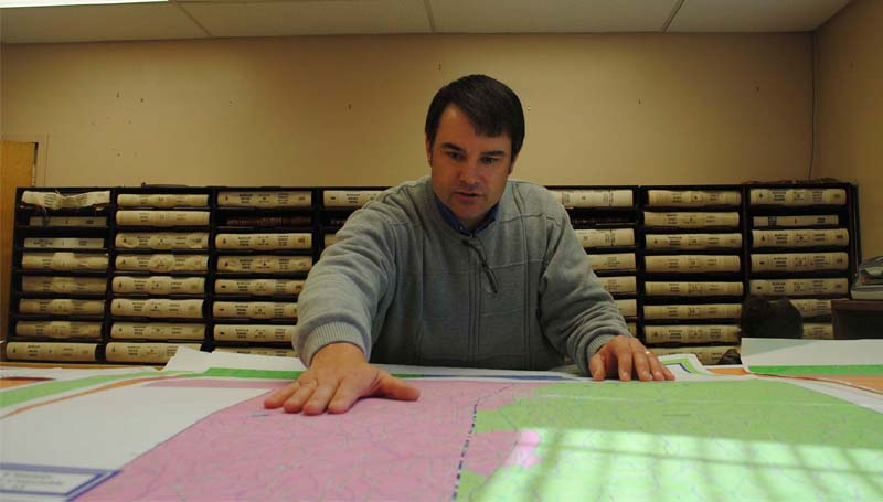 THE DAILY LEADER / JUSTIN VICORY / Lincoln County Circuit Clerk Dustin Bairfield examines maps outlining district lines in the county in an effort to determine voting precincts for federal elections in June.