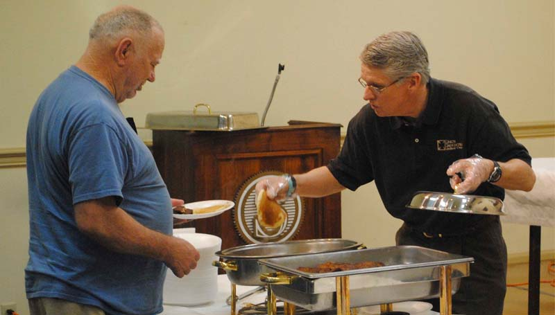 THE DAILY LEADER / RHONDA DUNAWAY / King's Daughters Medical Center CEO Alvin Hoover (right) serves up hot pancakes to Ralph Grice of Brookhaven in the State Room at State Bank this morning during the annual Tom Moak Memorial Pancake Day sponsored by the Brookhaven Servitium Club. Pancake Day is under way until 7 p.m. Plates are $5 each.