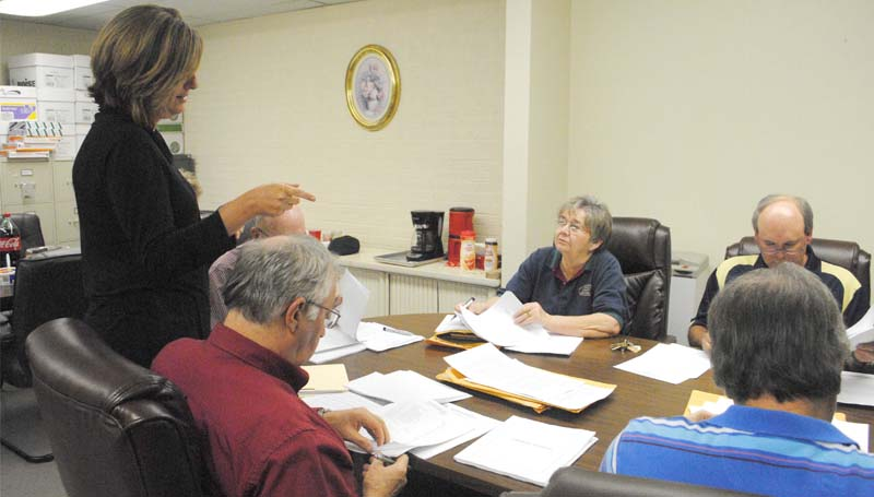 THE DAILY LEADER / RHONDA DUNAWAY / Lincoln County School District accountant Cheryl Shelby (left) goes over details of January 2014 financial statements with vice president of the school board Kay Coon (center, facing) and other board members at Monday's board meeting.