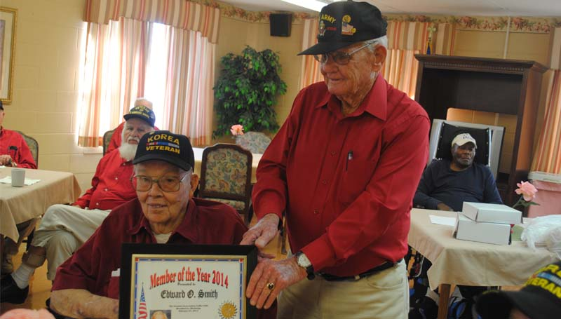 THE DAILY LEADER / JUSTIN VICORY / James Swager presents fellow veteran Edward O. Smith with the highest award offered by members of the Greatest Generation Coffee Club, the Member of the Year plaque. Smith received the award Friday afternoon at the Golden Living Nursing Home. Smith is a veteran of the Korean War.