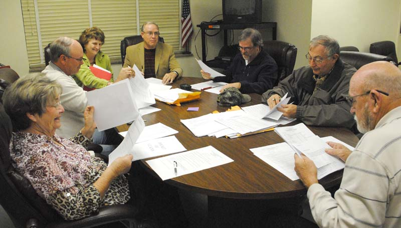 THE DAILY LEADER / RHONDA DUNAWAY / Lincoln County School Board members have approved 49 new board policies at their Monday meeting. Kay Coon, vice president; (from left) Ricky Welch, president; Regina East, administrative assistant; Terry Brister, superintendent; Johnny Hart, member; Michael Posey, secretary; and Jack Case, member, are shown reviewing the updated policies.