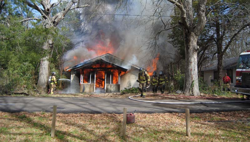 THE DAILY LEADER / TAMMIE BREWER / Brookhaven firefighters spray water on a burning house on Ford Lane Friday morning during a controlled burn. The city often uses properties that need cleaning up or that have been abandoned for the purpose of training firefighters.