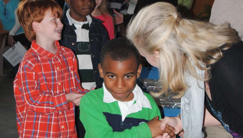 THE DAILY LEADER / TAMMIE BREWER / Brookhaven-Lincoln County Chamber of Commerce Programs Director Kay Burton (right) gives a handshake to Brookhaven Elementary third-grader Pierce Bridgeforth, while Holden Britt (left) receives a gift from Mississippi Scholar representative Marty Stroud Friday afternoon. Mississippi Scholar officials were at the school to bestow certificates and gifts to students who were deemed Mississippi Rising Scholars or Mississippi Star Scholars. Both Bridgeforth and Britt are Mississippi Star Scholars.