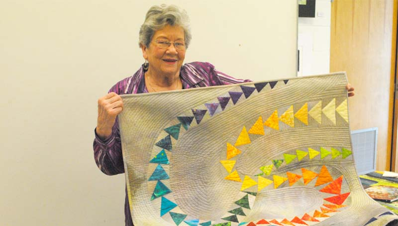 THE DAILY LEADER / RHONDA DUNAWAY / Fiber artist Martha Ginn displays a recent art-deco designed quilt at Monday's meeting of the Piecemakers Quilters Guild in the Lincoln County Library. Ginn is responsible for establishing Pine Belt Quilters in 1984 and the Mississippi Quilt Association in 1991.