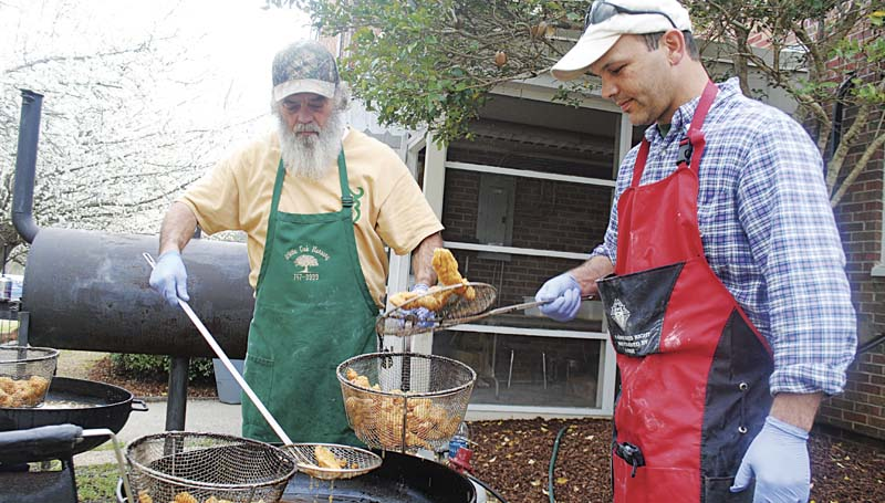 DAILY LEADER / JUSTIN VICORY / Timmy Nations (from left) and Myron Bartholomew fry batches of fresh fish Friday night as part of the Knights of Columbus annual Lenten fish fry at St. Francis of Assisi Church Parish Center. Members are preparing fish dinners every Friday until Easter as part of the religious observation.
