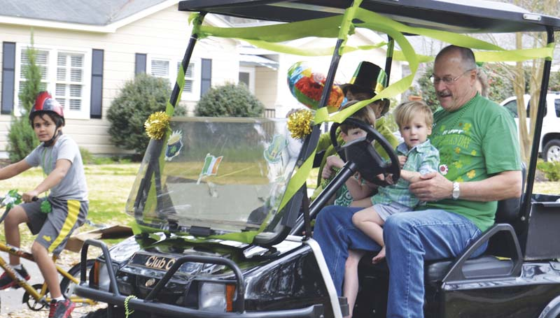 DAILY LEADER / RACHEL EIDE / Parade Grand Marshal John Branning Hewitt, 2, rides in the lap of his grandfather, Lester Bellah, in a golf cart leading the St. Patrick's Day Parade down South Church Street Saturday.
