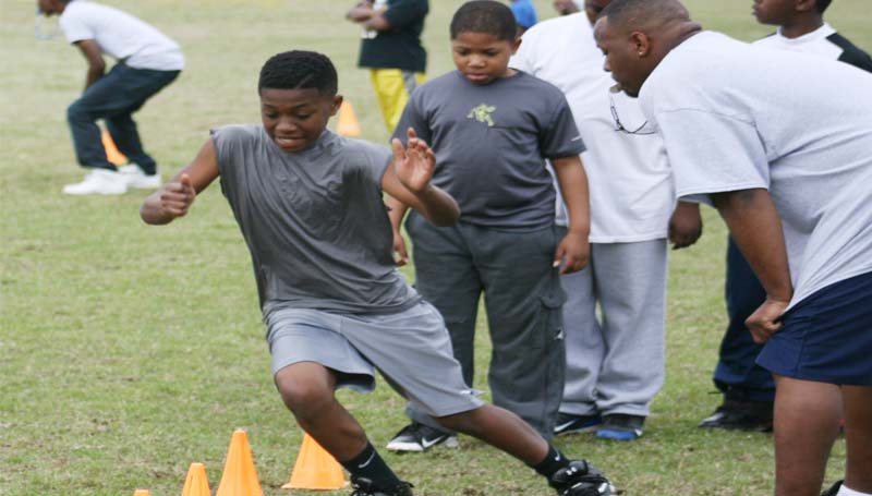 Jontavious Wilkinson practice hits his foot skills in a drill run as coach Jason Dixon (right) looks on during Saturday's Brookhaven Southern Wildcats pee-wee registration day at Lipsey Middle School.