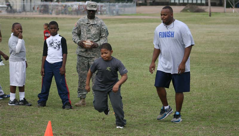 THE DAILY LEADER / MARTY ALBRIGHT / Nathan Lewis (above) runs a warm-up drill as coach Jason Dixon (right) looks on during Saturday's Brookhaven Southern Wildcats peewee registration day and mini camp at Lipsey Middle School.