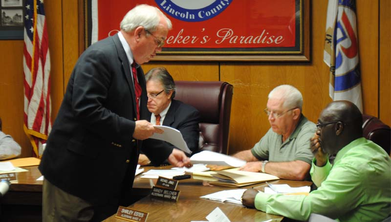 THE DAILY LEADER / JUSTIN VICORY / City Attorney Joe Fernald (front left) hands out an updated version of the city beer ordinance to City Clerk Michael Jinks, Alderman Randy Belcher and other board members Tuesday night. Looking on (in back) is Mayor Joe Cox.