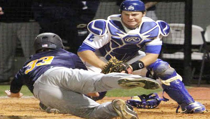 DAILY LEADER / SHERYLYN EVANS / Co-Lin catcher Logan Smith (25) blocks the plate to tag out Gulf Coast runner Matt Trigg (33) sliding in Game Two of the doubleheader.