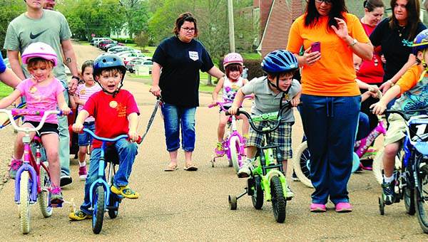"""THE DAILY LEADER / JUSTIN VICORY / A flurry of bikes, tricycles, scooters and even motorized vehicles circled around the block Wednesday morning as part of First United Methodist Church's annual """"Trikathon"""" event. Among the riders are (from left) kindergarten class members Lilly Jones, Riley Touchstone and Sawyer Boyd."""
