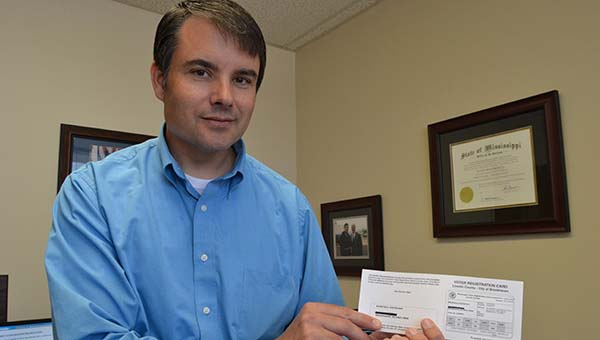 THE DAILY LEADER / RACHEL EIDE / Lincoln County Circuit Clerk Dustin Bairfield holds a sample of the voter registration cards that will go out in Monday's mail to county voters.