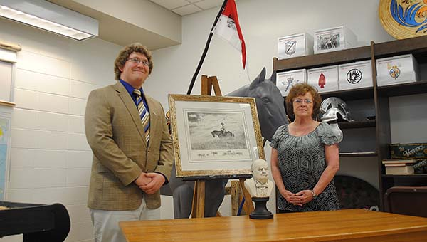 """Alex Berry presents this year's Centurion History Club fund drive winner, Patsy Berch of Hazlehurst, with her prize, """"Hawk on the Wing,"""" created by longtime artist Robert """"Shoofly"""" Shufelt. Berry is Berch's grandson."""