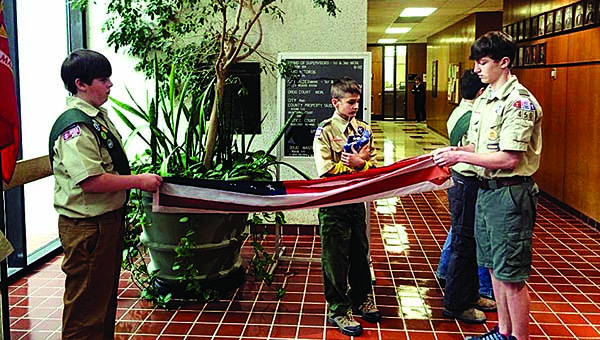 PHOTO SUBMITTED / Boy Scout Troop 450 members Tre Chapman (from left), Eli Marbury and Wesley Blazier fold a U.S. flag to be placed in a new flag depository box, which was donated by the Woodmen of the World organization in March.