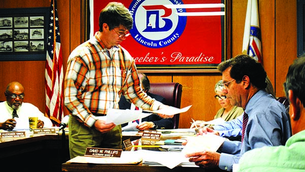 THE DAILY LEADER / JUSTIN VICORY / Mike McKenzie of WGK Engineering passes out bid paperwork to the board of aldermen for city work on Chickasaw Street.