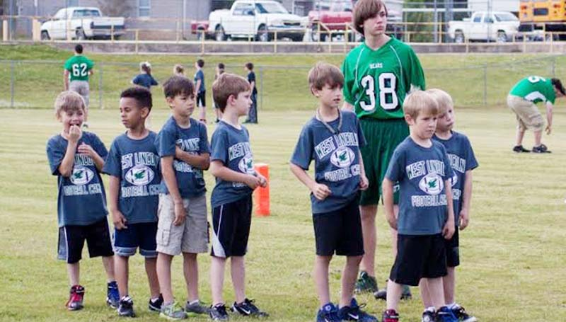 DAILY LEADER / TERESA ALLRED / The West Lincoln football player conducted a Pee Wee football camp for their Elementary kids last Thursday and Friday to teach them some drills. (Right photo) West Lincoln player Joey Mejia (left) watches Carson Temple kick the ball.