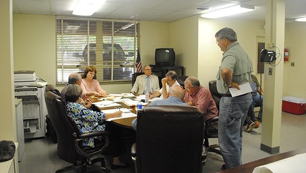 THE DAILY LEADER / RHONDA DUNAWAY / Lincoln County School District board members met Monday to discuss new buildings and 16th Section land bids. 16th Section Land Manager Stan Long (standing) discusses bids the district recently received. Meanwhile, Regina East (facing camera, left) opens sealed bids while Superintendent Terry Brister (facing camera, right) and other board members listen and ask questions.