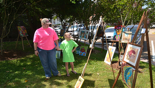 THE DAILY LEADER / RACHEL EIDE / Breann Rutledge of Brookhaven and Aubren Ezell, 8, of Ruth admire the Brookhaven Regional Arts Guild's art in Railroad Park during the Lincoln County Master Gardeners annual Gardening Extravaganza Saturday.