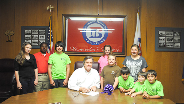 """DAILY LEADER / RHONDA DUNAWAY / Central Baptist Church Youth and Children's Ministry members and parents were on hand Monday as Mayor Joe Cox signed a proclamation designating the week of April 28 through May 2 as Purple-Ribbon Week in Brookhaven. Relay for Life organizer and member of Central Baptist Church Cindie Chambers said, """"We are asking the town to contribute by buying and displaying purple ribbons all over town."""" She said the ribbons are great for door wreaths and gift toppers. They are $5 and can be bought from any Relay for Life team members. All proceeds go to the American Cancer Society. For more information on purchase of the ribbons call Christi O'Neal, 601-748-0304. In the board room with Cox (center) are Central Baptist Church members  Katherine O'Neal (from left), Zaquavious Arnold, Pierce Chambers, Montana O'Neal, Jessica Gill, Alexander Santos, Olivia Clark, Maddox Chambers and Gabriel Santos."""
