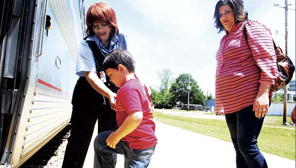 DAILY LEADER / JUSTIN VICORY / Mason Chavis, a preschooler at First United Methodist Church, receives some help getting onto the Amtrak train Thursday in Brookhaven as his mother, Patricia Carpenter (right), looks on. The entire preschool class, family members and staff rode the train from Brookhaven to McComb. For many, it was the first time they had ever set foot on a train.