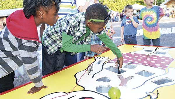 "DAILY LEADER / RACHEL EIDE / As Tahlasja Coleman, 6, (from left) watches intently, Jeremiah Everett, 8, performs ""surgery"" on the ""patient"" in the Operation Game at the King's Daughters Medical Center booth at the Lincoln County Relay for Life for the American Cancer Society Friday evening in Exchange Club Park. The game was built by Christopher Halley of Halley Construction and drawn and painted by University Medical Center nursing graduate Karlee Rushing."