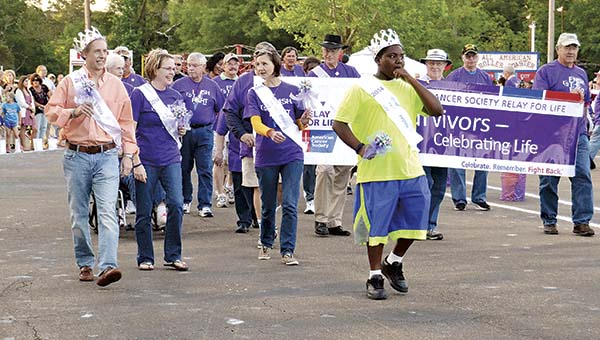 DAILY LEADER / RACHEL EIDE / Lincoln County Relay for Life royalty, (front from left) including King Jeff Michel, Queen JoAnna Sproles, Princess Maggie Cupit and Prince Zaquavius Arnold, lead the Survivors Walk at the event for the American Cancer Society Friday evening in Exchange Club Park.