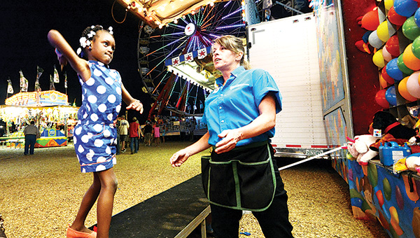 DAILY LEADER / KATIE WILLIAMSON / Kymauria Shannon, 3, throws darts at balloons during the Mississippi Spring Fest and Fair Wednesday at the Lincoln County Civic Center. The fair continues through Sunday, May 11.
