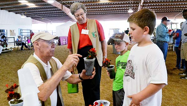 "DAILY LEADER / RACHEL EIDE / Homer Richardson (from left) and Edna Bishop of the Lincoln County Master Gardeners help Brody Taggart, 7, and Bryce Smith, 8, pot begonias Saturday at Farm Day at the Fair activities at the Mississippi Spring Fest and Fair. The boys both had definite plans for their plants. ""I'm going to give this to my mom,"" aid Brody, obviously with Sunday being Mother's Day in mind. ""I'm going to nurse mine,"" said Bryce."