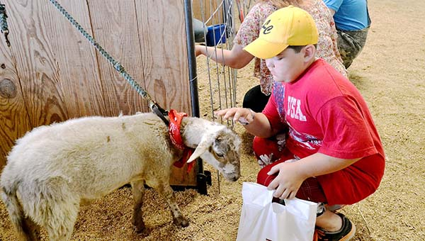 Calvin Thomasee, 9, makes friends with a goat during Farm Day at the Lincoln Civic Center stall barn.