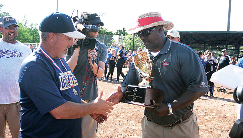 Bogue Chitto head coach, Scott Leggett (left) shakes hands with MHSAA Assistant Director Lonnie Tillman before accepting the state championship trophy.