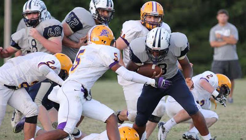 DAILY LEADER / Photos by AMY RHOADS / (Top photo) Bogue Chitto's Deion Williams (8) lowers his shoulder to plow through a St. Aloysius defender last Thursday. (Right photo) Enterprise Trae Roberts (44) gains positive yards against the Bobcats in the Bogue Chitto's spring jamboree at Troy Smith Field.