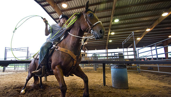 DAILY LEADER / KATIE WILLIAMSON / Mark Curry  rides header during team roping practice at the Lincoln County Civic Center arena on Wednesday. Team roping is a rodeo event that involves two riders. The header ropes the front of the steer and the heeler ropes the steer on its hind legs once the header has control.