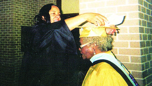 DAILY LEADER / PHOTO SUBMITTED / Hightower being assisted by an Alcornite putting her cap on just before the Golden Certificate ceremony.