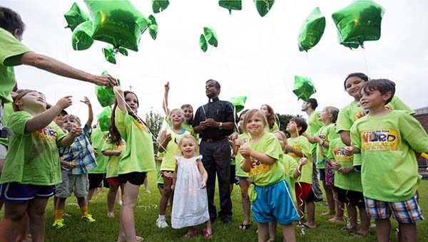 """DAILY LEADER / KATIE WILLIAMSON / Father Alphonse Arulanandu leads the St. Francis of Assisi Vacation Bible School in releasing balloons outside of the parish community center on Thursday. The balloons had stickers with the theme for the event, """"Weird Animals; Jesus's love is one of a kind."""""""