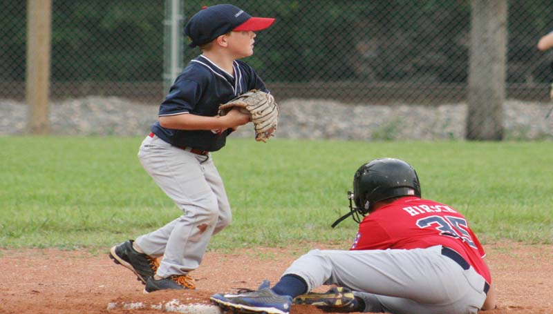 """DAILY LEADER / MARTY ALBRIGHT / Lincoln County Nationals shortstop Noah Gatlin steps on second base to record the out before Lincoln County Americans' Zachery Hirsch could reach Monday night in Dixie Youth action at Leroy """"Cowboy"""" Jones Memorial Field."""