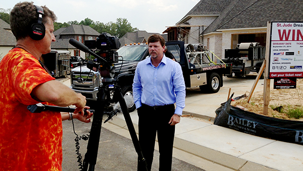 PHOTO SUBMITTED / Reed's Metals of Brookhaven recently donated $10,000 worth of metal roofing materials to be used in the construction of St. Jude's Dream Home located in Flowood. The home will be used as a fundraiser to aid St. Jude's $1.9 million dollar daily operating budget and tickets are being sold for $100 each. The home is valued at an estimated $415,000. If potential buyers purchase a ticket before July 4, 2014, the buyer will also be entered to win a $1000 gas card donated by Butler Snow. Tickets may be purchased at any Jackson area Regions Bank, Ross Furniture in Flowood, online at www.dreamhome.org or over the phone at 1-800-371-6789. The winner will be drawn on Sept. 21, 2014 on WLBT. Pictured is Bernie Reed, president of Reed's Metals, being interviewed by a WLBT news crew near the construction site.