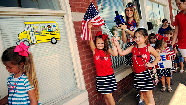 Wearing matching outfits (center, from left) Emma King and Emma Barrett share a flag during FBC's Independence Day parade. Also pictured are (front) Kaylee Thornton; (looking backwards) Gracie Fitzsimmons; (far back) Brooke Williams and Cohen Leggett.
