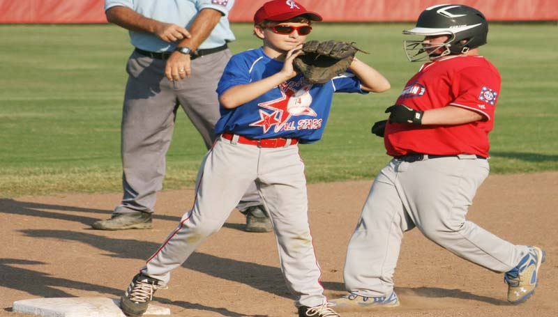 DAILY LEADER / MARTY ALBRIGHT / Lincoln County Americans runner Chase White (right) advances to third on a pass ball while Copiah's third baseman Tac Collum waits on the play in Dixie Youth AAA action at Gallman.